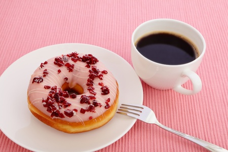 sweet cranberry donut with a cup of coffee photo