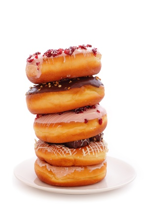 A stack of donuts on a white background including chocolate icing, sprinkles, coconut and glaze photo