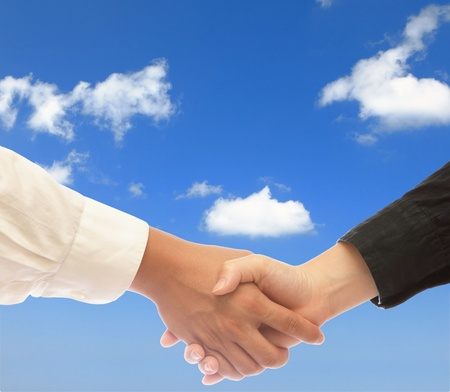 enterprises: shake hands with blue sky Stock Photo