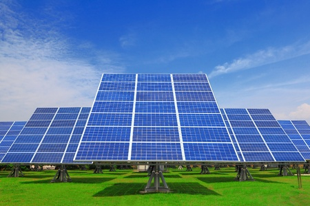 solar cells: Solar Panel with green grass and beautiful blue sky Stock Photo