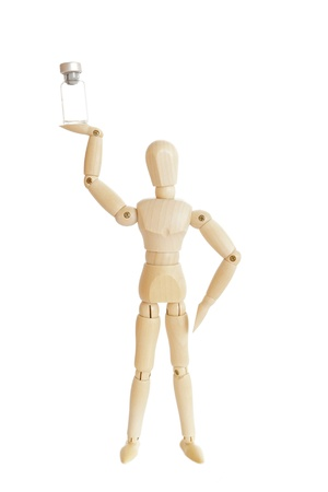 wooden doll: Wooden figure holding medicine injector bottle Stock Photo