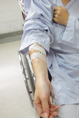 Patient hand with an intravenous drip before surgery in an operation room photo