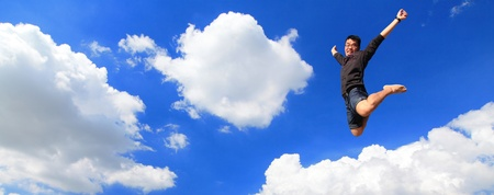 Happy young Man jumping with sky background photo
