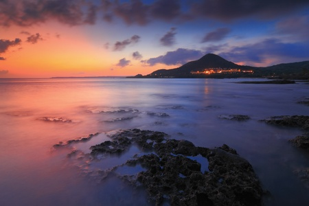 Amazing beautiful sunset reflection on the sea with rock, wave and mountain Stock Photo - 11241210