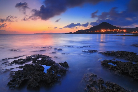 Amazing beautiful sunset reflection on the sea with rock, wave and mountain photo