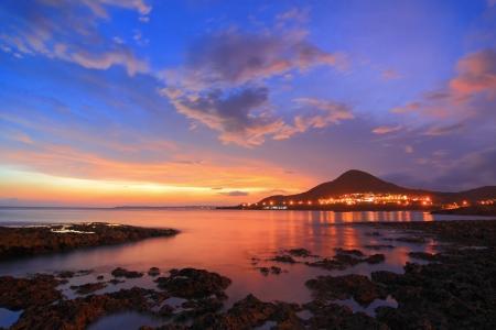 Geweldige prachtige zonsondergang reflectie op de zee met rock, wave en de bergen