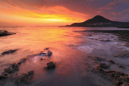Amazing beautiful sunset reflection on the sea with rock, wave and mountain Stock Photo - 11343988