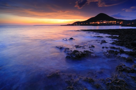 Amazing beautiful sunset reflection on the sea with rock, wave and mountain Stock Photo - 11343940
