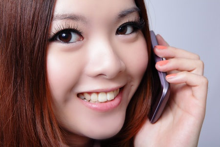 Young woman speaking cell phone with sweet smile, model is a asian beauty photo