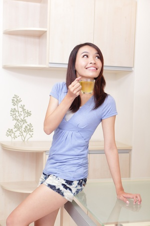 Happy Young Girl relax drink tea with home background, model is a asian beauty Stock Photo - 11875608