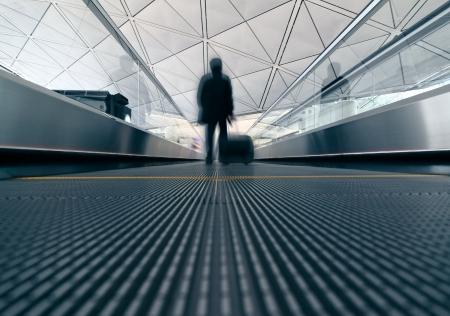 airport arrival: passenger (Man) rushing through an escalator in airport terminal, blue tone