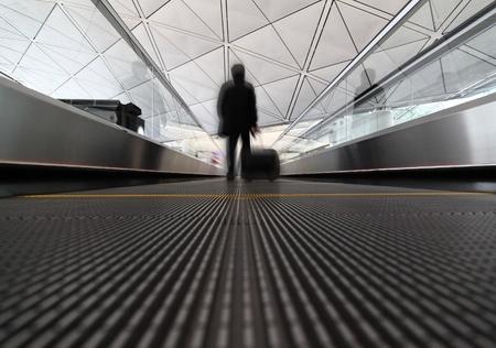 passenger (Man) rushing through an escalator in airport terminal photo