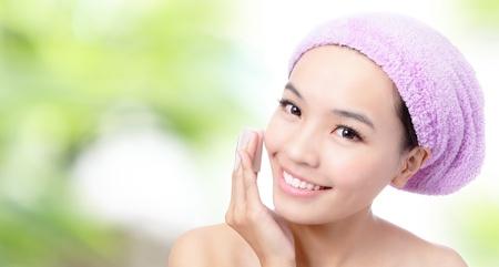 Close-up van jong meisje te verwijderen make-up door het reinigen van katoen met groene achtergrond, Model is een Aziatische schoonheid