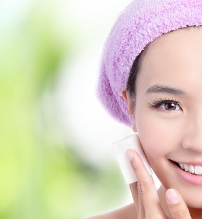 닫기 어린 소녀의 녹색 배경면 클렌징으로 메이크업을 제거, 모델은 아시아의 아름다움