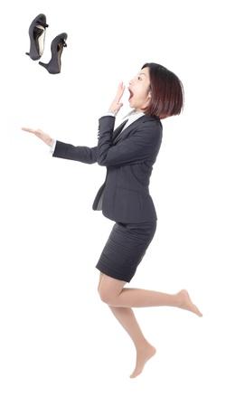 젊은 비즈니스 여자 점프와 흰색 배경에 고립 된 공기에 높은 굽 신발을 던져