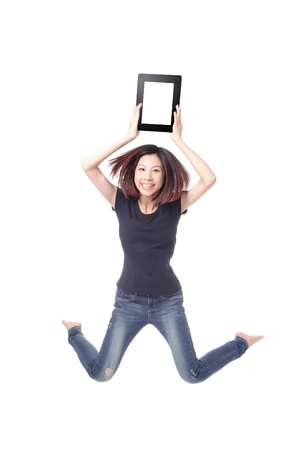 Young beauty happy jump and showing tablet pc in the air isolated on white background, model is a cute asian photo