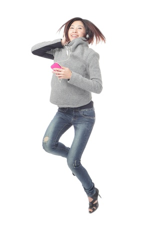 Young Girl happy jump and listen music by mobile phone isolated on white background, model is a asian beauty Stock Photo - 12033988