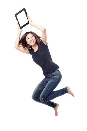 Mladá kráska šťastný skok a ukazuje tablet pc ve vzduchu na bílém pozadí, model je roztomilý asijské