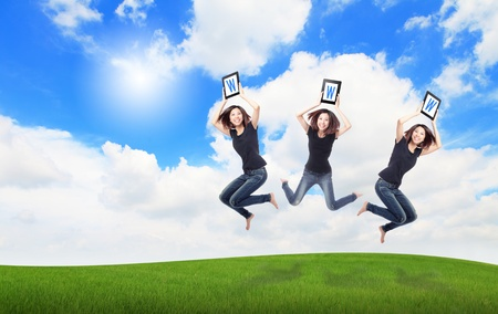 Happy Girl Jump and show touch pad computer (with WWW text) on the meadow with blue sky and white cloud, for cloud computing concept photo