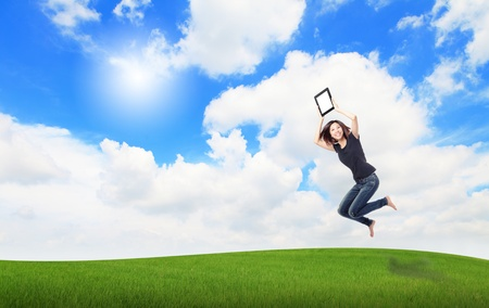 Happy Girl Jump and show touch pad computer on the meadow with blue sky and white cloud, , for cloud computing concept photo