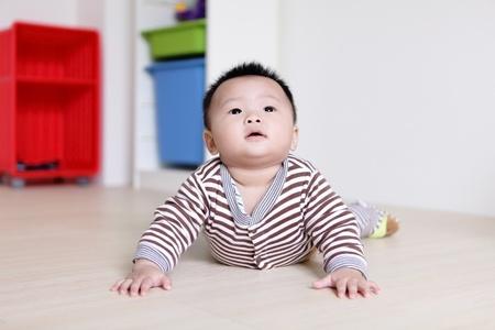 bebe gateando: Lindo beb� gateando en del cuarto de estar con el fondo de su casa, el beb� es un beb� asi�tico lindo Foto de archivo