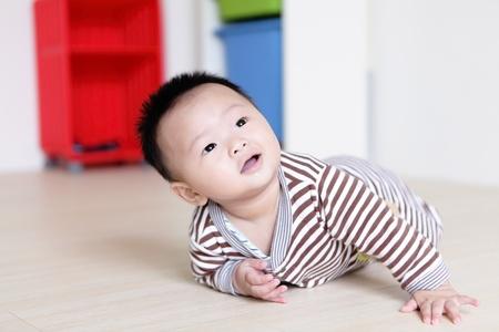 bebe gateando: Lindo bebé gateando en del cuarto de estar con el fondo de su casa, el bebé es un bebé asiático lindo Foto de archivo
