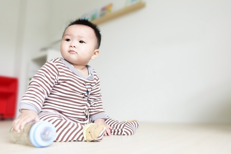 귀여운 아기가 왼쪽을보고 집 배경으로 자신의 젖병을, 아이는 귀여운 아시아 소년 아기입니다