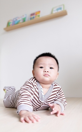 Cute Baby crawling on living room floor with home background, baby is a cute asian child photo
