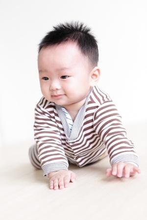 bebe gateando: Lindo beb� gateando en del cuarto de estar con el fondo de su casa, el beb� es un ni�o asi�tico lindo