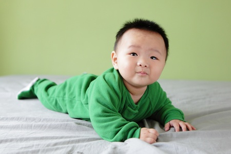 Cute Baby Look Up forward with green background, Baby is a cute asian child Stock Photo - 12209144