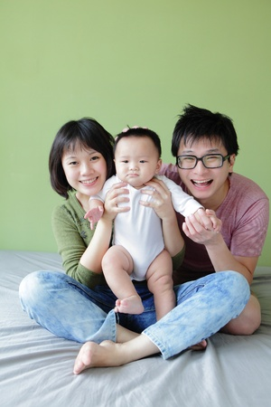 Mother, father and small baby smile face with green background. Model are asian family. photo