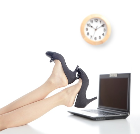 Relax Time in office, business woman take off high heels shoes with office background and a clock photo