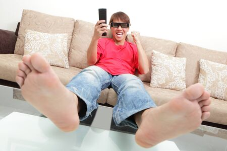 exciting young man watch 3D LCD TV with eye glass in a living room Stock Photo - 12209205