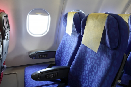 airline: Airplane blue seat and window inside an aircraft
