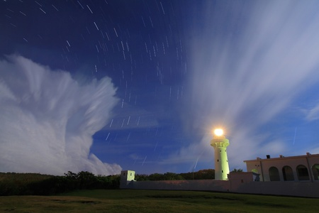 beam of light: lighthouse in the night with moving star and floating cloud