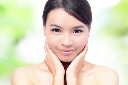 close up of Beauty woman Face and hand touch her face with green background, model is a beautiful asian girl photo
