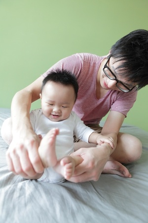 Young Father Happy Play with His Baby (an asian family) with green home background photo