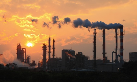 Air pollution smoke from pipes and factory with sunset background