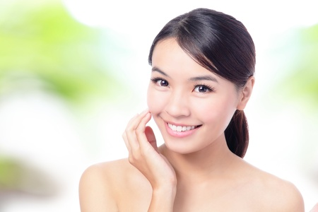 close up of Beauty woman Face and hand touch her face with green background for skin care concept, model is a beautiful asian girl photo
