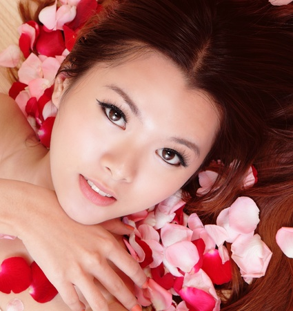 sexy asian woman: Asian beauty Girl smiling close-up with rose background, Beautiful young woman touching her face looking to the camera Stock Photo
