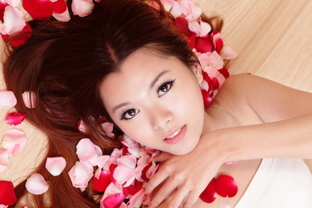 sexy asian girl: Asian beauty Girl smiling close-up with rose background, Beautiful young woman touching her face looking to the camera Stock Photo