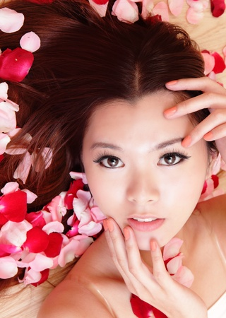 Asian beauty Girl smiling close-up with rose background, Beautiful young woman touching her face looking to the camera photo