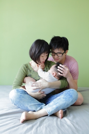 Young parents looking at their baby with green background, model are asian family photo
