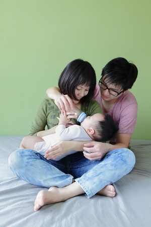 a mother and father feeding their baby bottle with green background, model are asian family