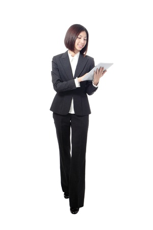 full length businesswoman smiling using touch pad tablet pc isolated on white bckground, model is a asian beauty photo
