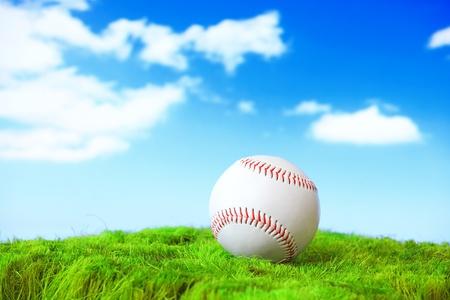 beisbol: Base Ball en campo de hierba verde con fondo de cielo azul Foto de archivo