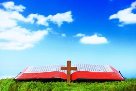 bible ouverte: Briller Open Bible et croix sur l'herbe avec fond de ciel