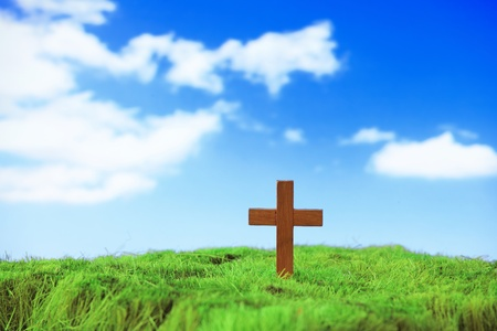 wood cross on green grass with blue sky and white cloud Stock Photo - 12527543