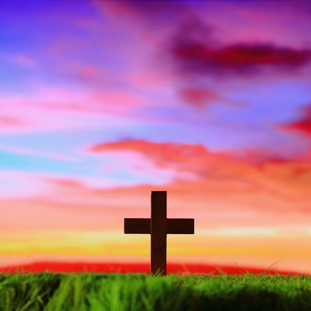 christian symbol: cross silhouette on grass with sunset background