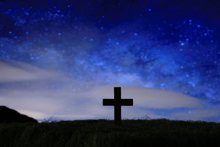 wood cross over a dark night starry sky Stock Photo
